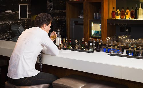 バーで一人酒を飲む男性