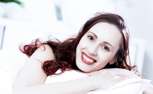 ベッドで寝る笑顔の女性