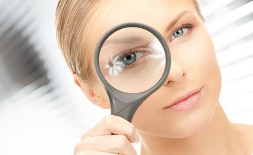 虫眼鏡で注意深く見る女性