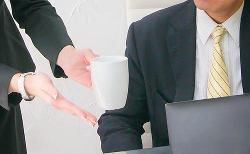 上司にコーヒーを出す女性