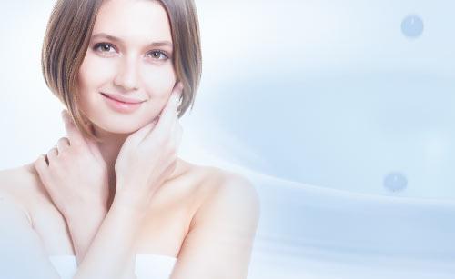 乳液と顔に手を当てる女性