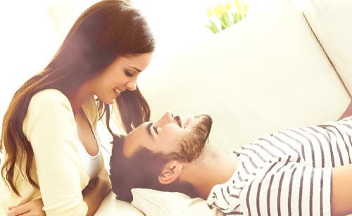 ソファーで寝る彼氏と笑顔で見下ろす彼女