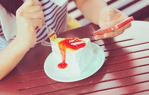 ケーキを食べながらスマホを食べる女性