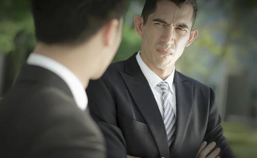 深刻な顔で注意するスーツ姿の男性