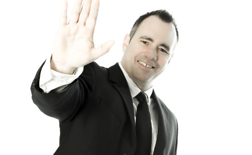 手をあげ帰宅しようとするスーツ姿の男性