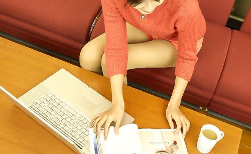 カタログを見ながらパソコンで調べ物をする女性