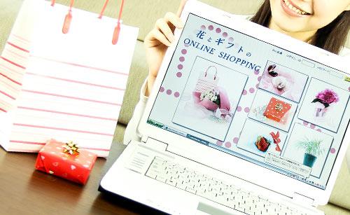 インターネットで購入した商品とパソコンを見せる女性