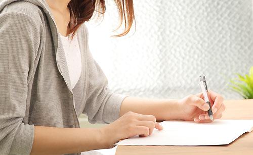 紙に思いを書く女性