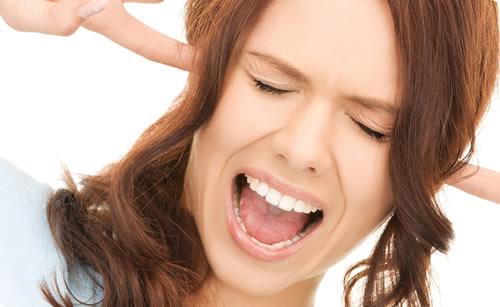 人差し指で耳を押さえる女性
