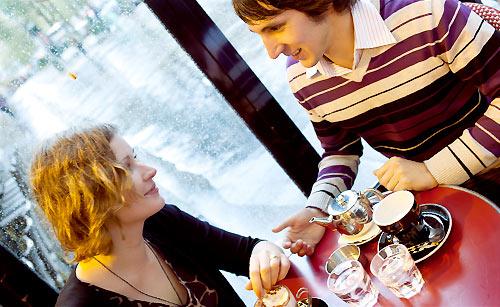 雨の中、カフェでデートを楽しむカップル