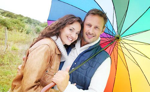 女性を傘に入れてあげる男性