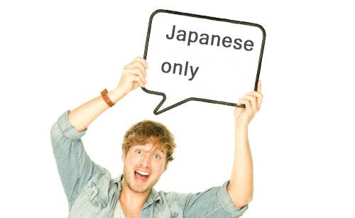 Japanese onlyの札を持ち上げる男性