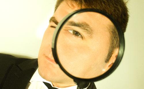 虫眼鏡から覗く男性