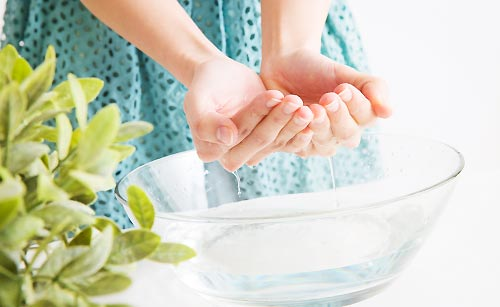水で顔を洗う女性