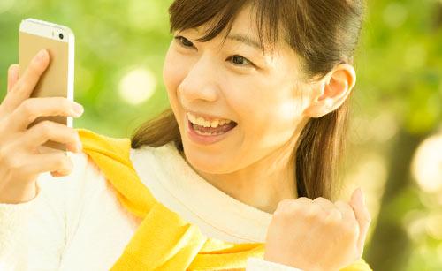 携帯を見る笑顔の女性