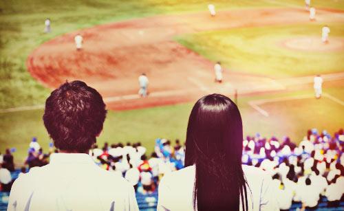 野球の試合を観戦するカップル