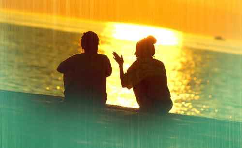 夕暮れに海で座るカップル