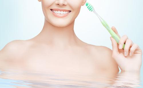 お風呂で歯磨きをする女性