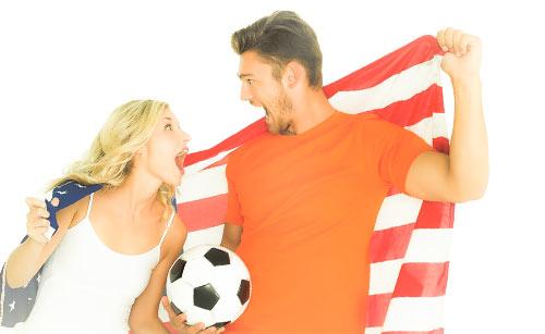サッカーボールを持ちながら国旗を背負うカップル