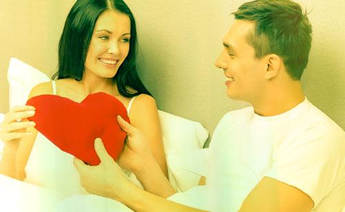 ベッドでハートを持つ女性と男性