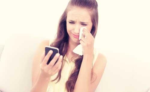 泣きながらメールをする女性