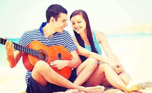 夏の海でギターを楽しむカップル