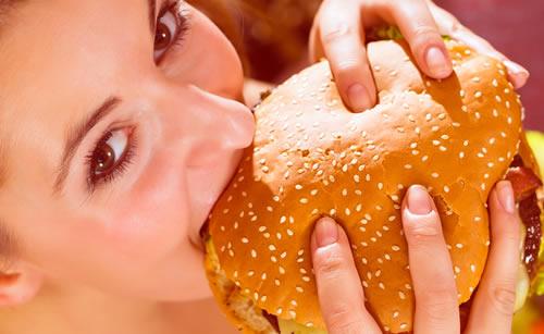 ハンバーガーを食べる早食いの女性