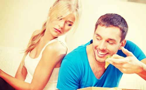 ダイエット中の女性の前でピザを食べる男性