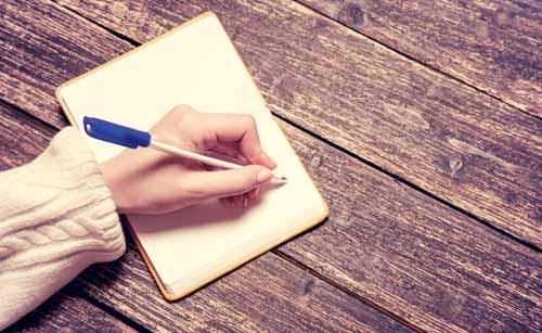 紙に書く女性の手