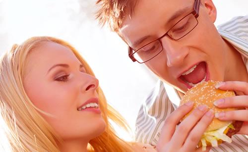 ハンバーガーを美味しそうに食べるカップル