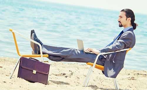 砂浜でパソコンを使う男