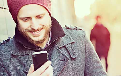 笑顔でメールを送る男