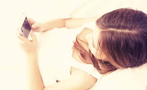 寝る前にスマホでSNSを見る女性