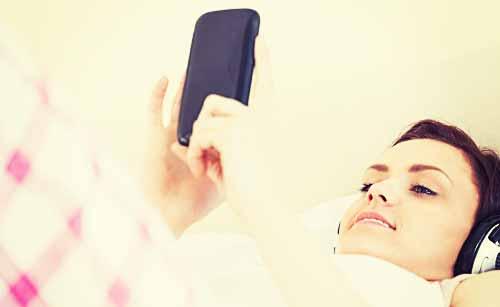 寝ながらスマホを使う女性