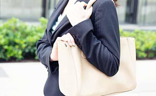 鞄を小脇に抱える女性