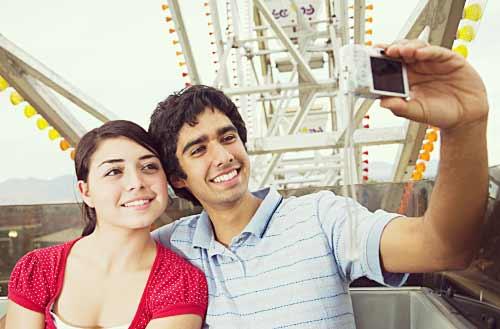 遊園地で記念撮影するカップル