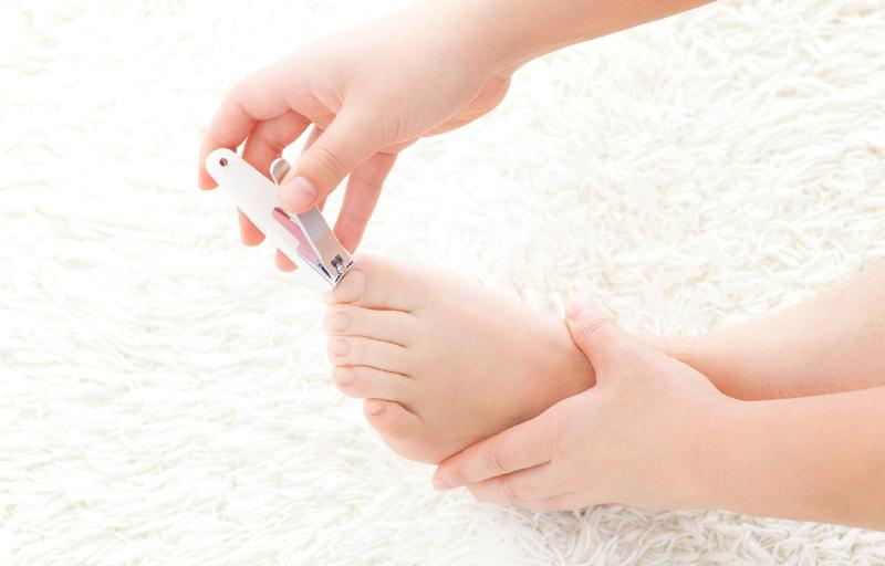 足の爪を切る女性