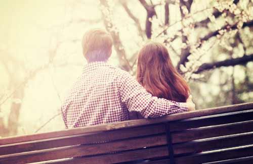 桜を見つめ物思いにふけるカップル