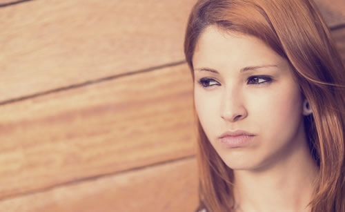 不機嫌な表情で遠くを見つめる女性