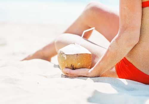 ココナッツジュースを横に海を眺める女性