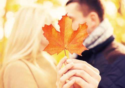 紅葉で隠してキスをするカップル