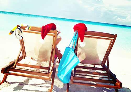 サンタ帽をかぶり海を眺めるカップル