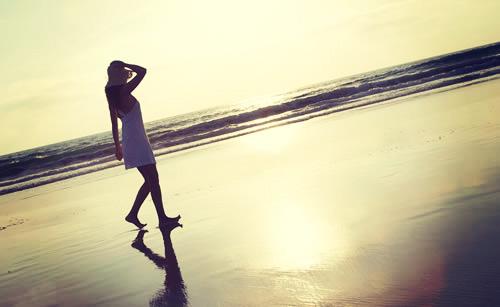 朝日が登る海岸線を歩く女性