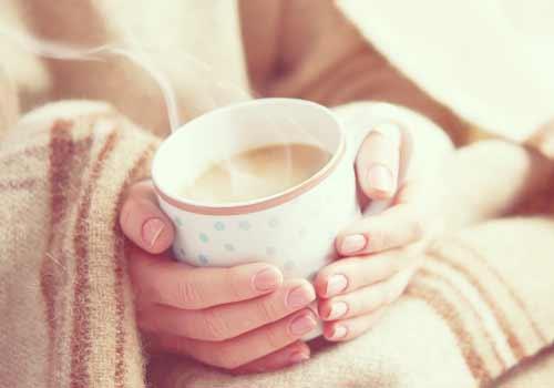 温かい飲み物を持つ女性