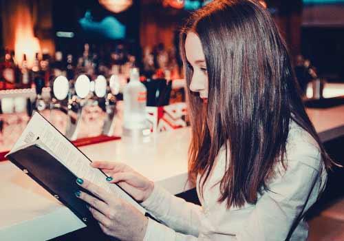 バーでメニューを読む女性