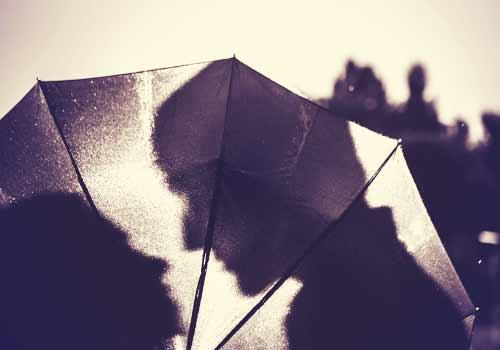 傘の影で言葉を交わす男女