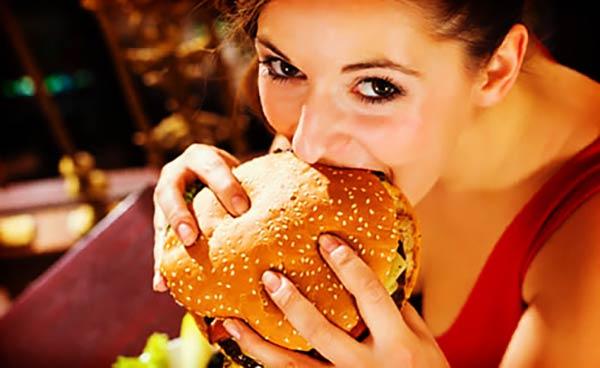 周りを気にせずハンバーガーを頬張る女性