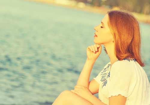 海辺で黄昏る女性