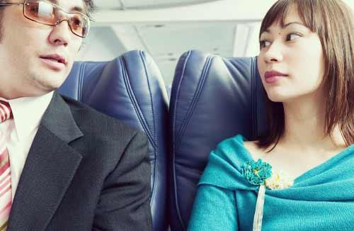 飛行機の席で目を合わせる男と女