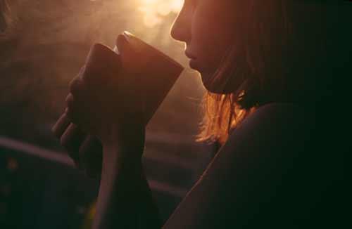 暗い部屋でコーヒーを飲む女性